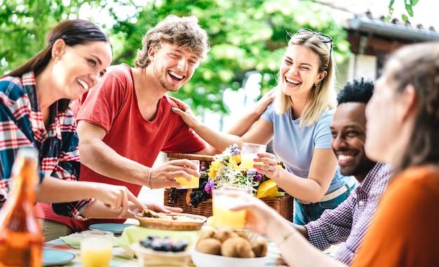 Giovani uomini e donne felici che tostano un sano succo di frutta arancione al picnic della fattoria