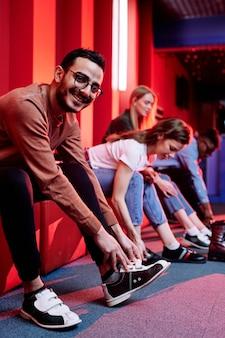 Felice giovane uomo di razza mista in abbigliamento casual e i suoi amici sullo sfondo si preparano a giocare a bowling mentre si cambiano le scarpe
