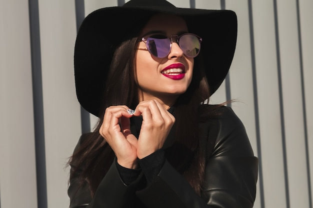 Felice giovane modella che indossa occhiali alla moda e cappello, facendo il simbolo del cuore con le mani per strada