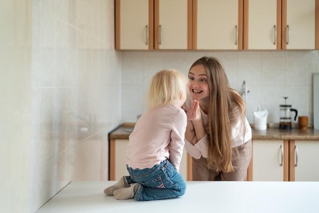 Felice giovane mamma e piccola figlia che ridono in cucina.