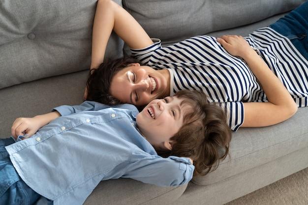 Felice giovane mamma e figlio ragazzino rilassante sul divano di casa