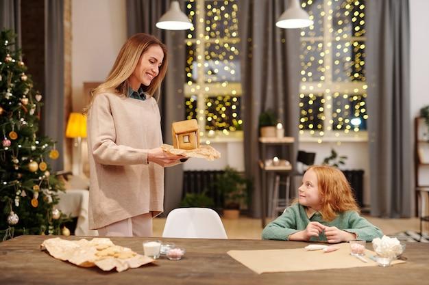 Felice giovane madre in abbigliamento casual che trasportano casa di marzapane fatta in casa mentre si avvicina alla sua piccola figlia carina