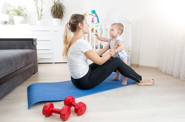 Felice giovane madre che fa yoga con il suo bambino sul pavimento in soggiorno