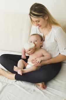 Felice giovane madre e il suo bambino che mangiano dalla bottiglia