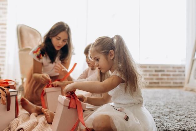 La giovane madre felice e le sue due affascinanti figlie in bei vestiti si siedono sul tappeto e aprono i regali di capodanno nella stanza luminosa e accogliente.
