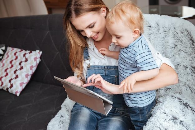 Felice giovane madre con il suo figlioletto seduto e usando il tablet sul divano