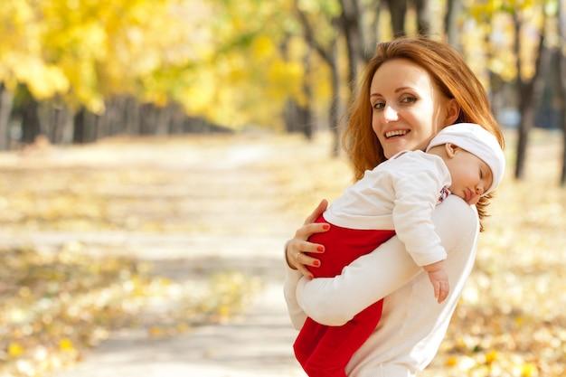 Felice giovane madre con bambino addormentato sulle mani che cammina nel parco autunnale