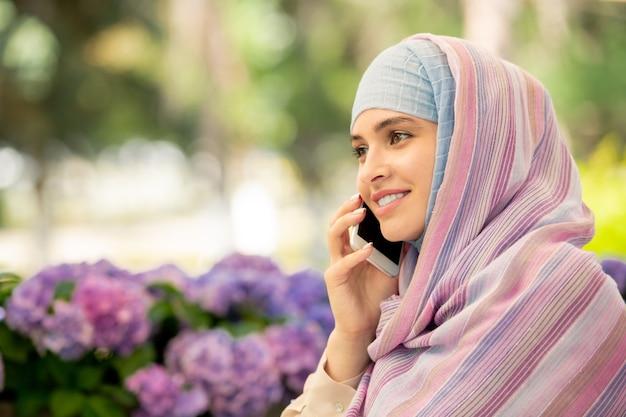 Felice giovane donna musulmana con lo smartphone a parlare con qualcuno mentre si riposa in ambiente urbano