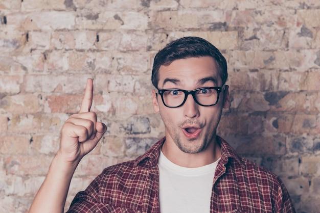 Felice giovane nerd ragazzo alzando il dito che ha un'idea