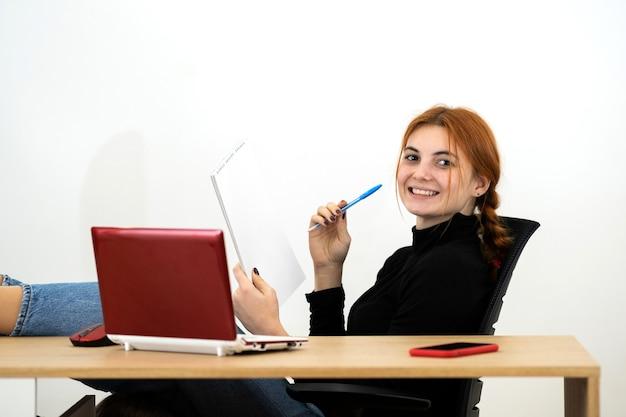 Felice giovane impiegato donna seduta rilassata con i piedi sul tavolo dietro la scrivania con il computer portatile