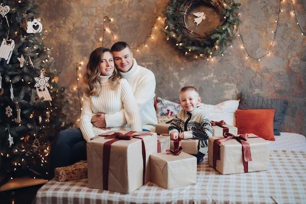 Felici giovani genitori e bambino seduto sul letto con molte scatole regalo vicino a loro e albero di natale