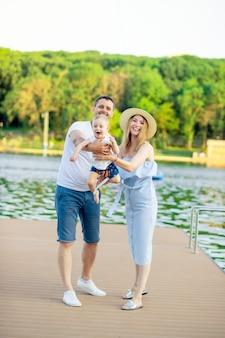 I giovani genitori felici mamma e papà con il loro bambino camminano in estate vicino all'acqua in riva al mare sull'argine e si divertono, lanciando il bambino come un aereo