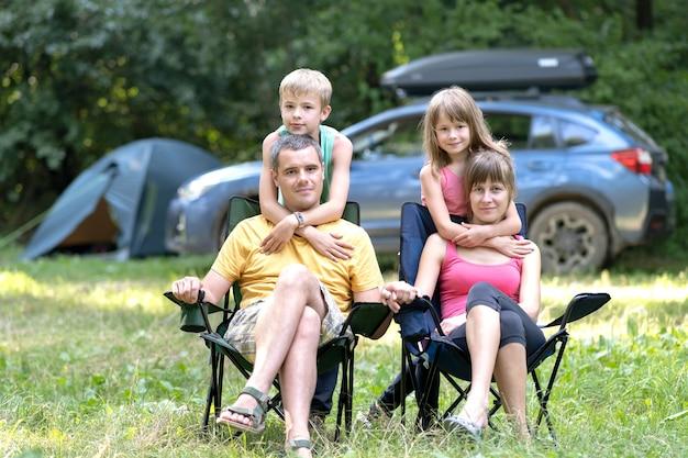 Giovani genitori felici e i loro figli che riposano insieme in campeggio in estate.