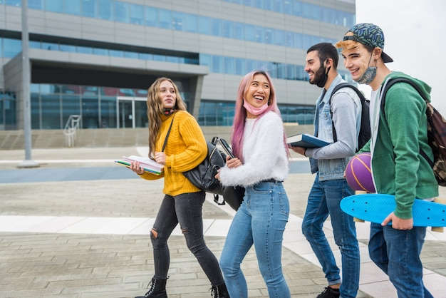 Giovani felici che si incontrano all'aperto e indossano maschere per il viso durante la pandemia covid-19