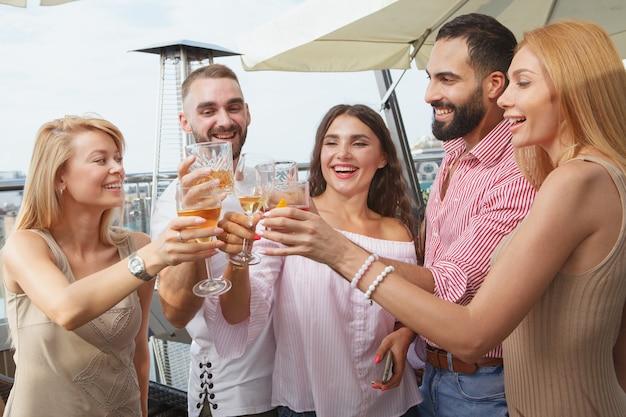 Giovani felici che urlano di gioia, brindano con i bicchieri, celebrano una festa sul tetto