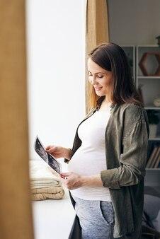 Felice giovane donna incinta in piedi dal davanzale della finestra in soggiorno e guardando le foto ad ultrasuoni del suo bambino fatte nelle cliniche