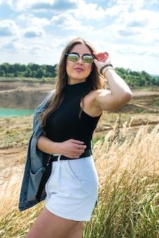 Felice giovane donna graziosa che gode del paesaggio vicino al campo verde nel periodo estivo