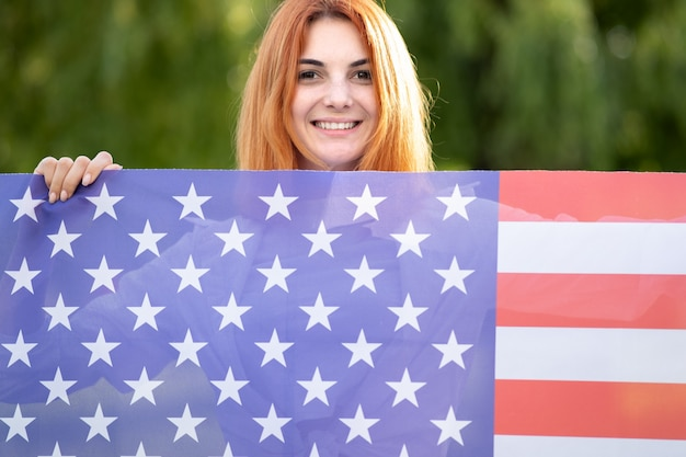 Felice giovane donna dai capelli rossi in posa con la bandiera nazionale usa in piedi all'aperto nel parco estivo.