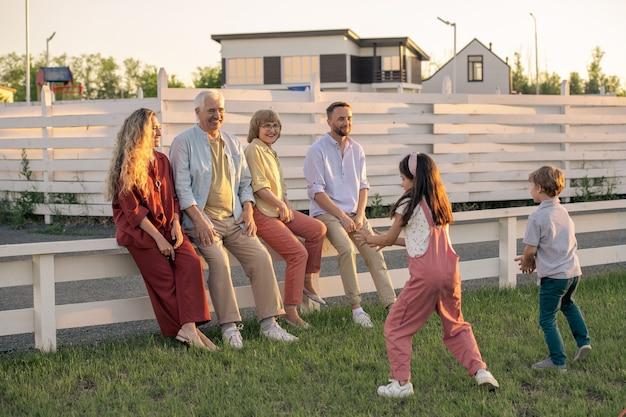 Coppie giovani e anziane felici che si siedono sul recinto bianco davanti a due bambini