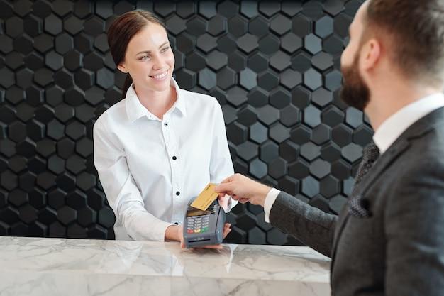 Felice giovane assistente di negozio che tiene macchina di pagamento mentre guarda uomo d'affari che paga per nuovi vestiti in boutique