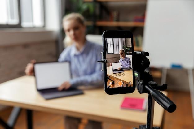 Felice giovane imprenditrice intelligente riprese tutorial educativi o condivisione di competenze professionali. concentrarsi sullo schermo del telefono. foto di alta qualità