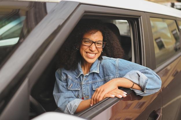 Felice giovane donna afroamericana sorridente autista dai capelli neri con gli occhiali seduto nella nuova auto marrone