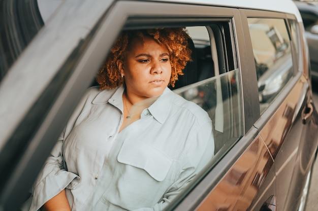Felice giovane donna afroamericana sorridente autista dai capelli afro rosso seduto in una nuova auto marrone sorridente