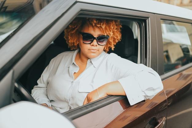 Felice giovane sorridente donna afroamericana rosso autista dai capelli afro in occhiali da sole seduto in new