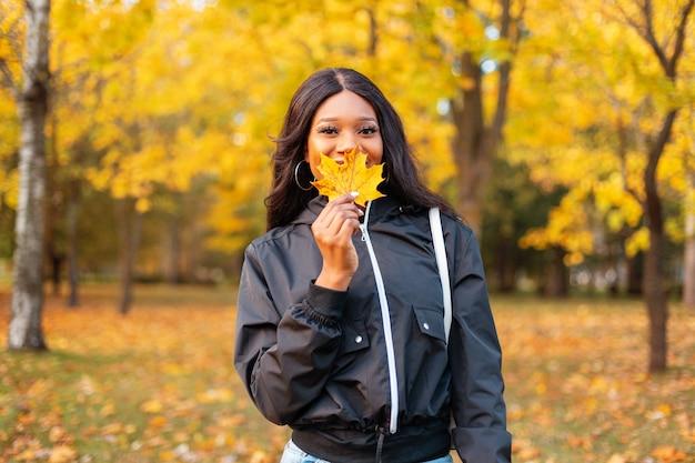 Felice giovane ragazza nera sorridente in giacca casual alla moda si copre il viso con una foglia autunnale gialla nel parco con fogliame dorato