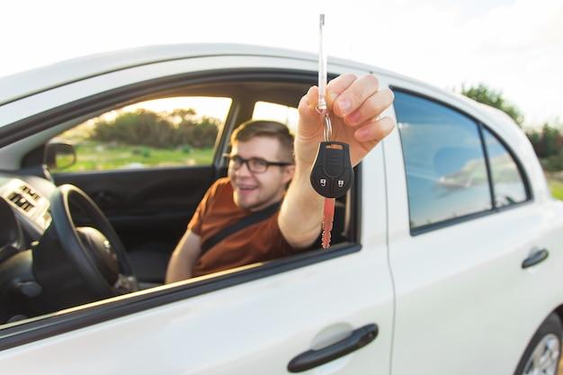 Felice giovane uomo sorridente seduto all'interno di un'auto nuova con le chiavi.