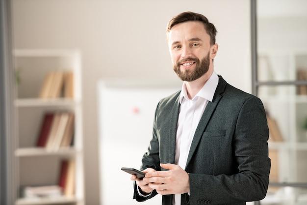 Felice giovane manager sorridente o agente con lo smartphone