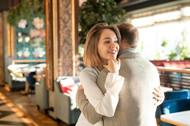 Felice giovane donna sorridente che abbraccia il suo affettuoso fidanzato mentre entrambi esprimono amore l'un l'altro nel lussuoso ristorante