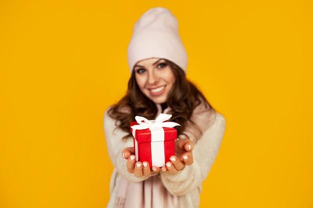 Felice giovane donna sorridente tenendo e tenendo il contenitore di regalo rosso davanti, offrendo e dando regali di natale. una ragazza con un maglione guarda e fa un regalo.