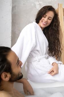 Felice giovane donna sorridente in accappatoio bianco a parlare con suo marito mentre era seduto davanti a lui sulla vasca da bagno