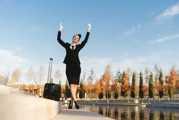 Felice giovane hostess in uniforme guarda il cielo, con una valigia, in attesa del suo volo