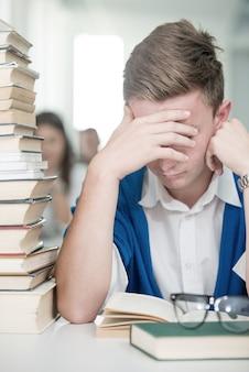 Giovani studenti felici che studiano nella biblioteca universitaria con la pila di libri