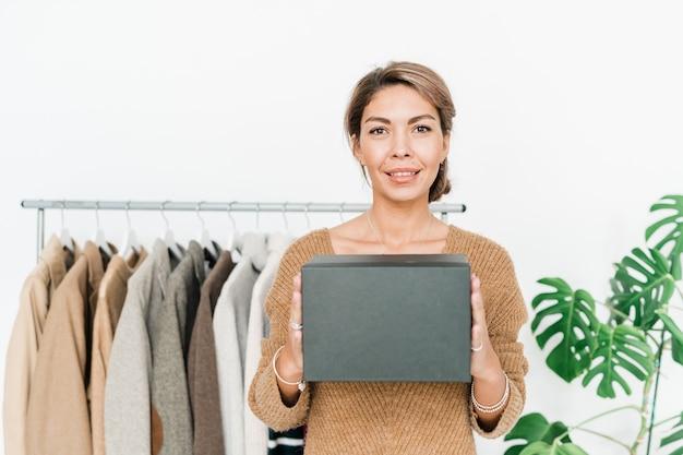 Felice giovane donna alla moda in pullover casual che tiene scatola nera dal petto