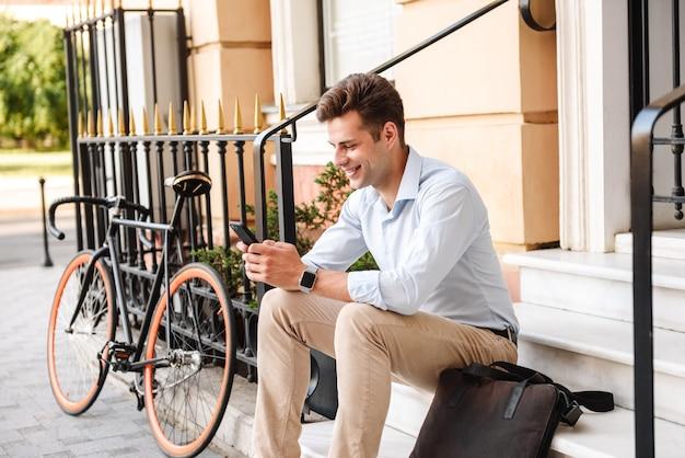 Felice giovane uomo elegante vestito in camicia seduta