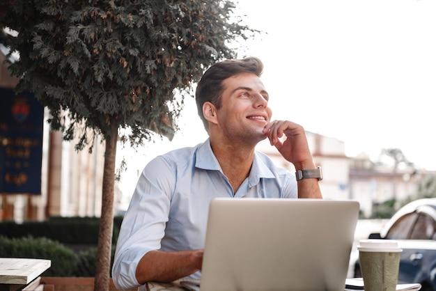 Felice giovane uomo alla moda che lavora al computer portatile