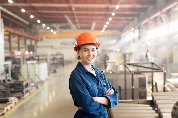 Felice giovane operaio di sesso femminile di successo della fabbrica in abbigliamento da lavoro e casco che incrocia le braccia sul petto