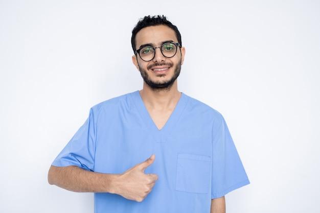 Felice giovane chirurgo maschio di successo o medico in uniforme blu che mostra il pollice in su mentre ti guarda con un sorriso