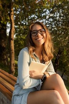Felice giovane ragazza adolescente con zaino seduti all'aperto