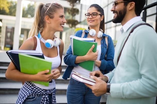 Felici giovani amici universitari che studiano insieme al college