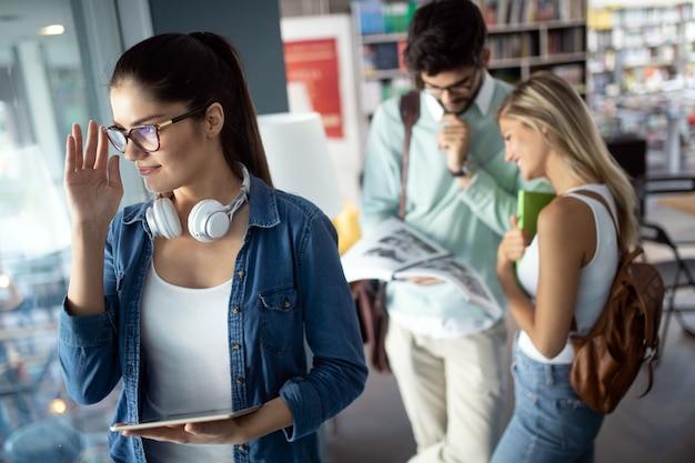 Giovani studenti universitari felici che studiano con i libri all'università. gruppo di persone al college