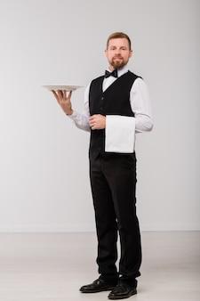 Felice giovane cameriere in abito elegante e papillon che tiene asciugamano pulito bianco e piatto per gli ospiti del ristorante