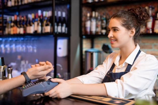 Felice giovane cameriera che tiene macchina di pagamento sul bancone mentre guarda uno dei clienti che pagano per bere o cibo