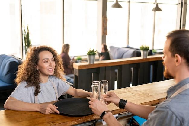 Felice giovane cameriera con vassoio guardando il suo collega da contatore mettendo due bicchieri d'acqua per i clienti