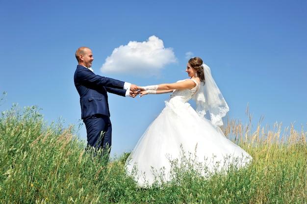 Felice giovane sposi in piedi sulla cima di una collina su uno sfondo di cielo azzurro con nuvole che tengono le mani.