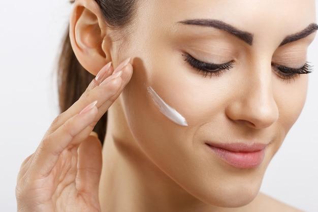 Giovane donna felice che applica crema alla sua faccia skincare e concetto dei cosmetici