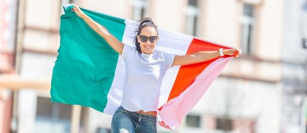 Felice giovane donna celebra la vittoria dell'italia su una strada tenendo una bandiera nelle sue mani.
